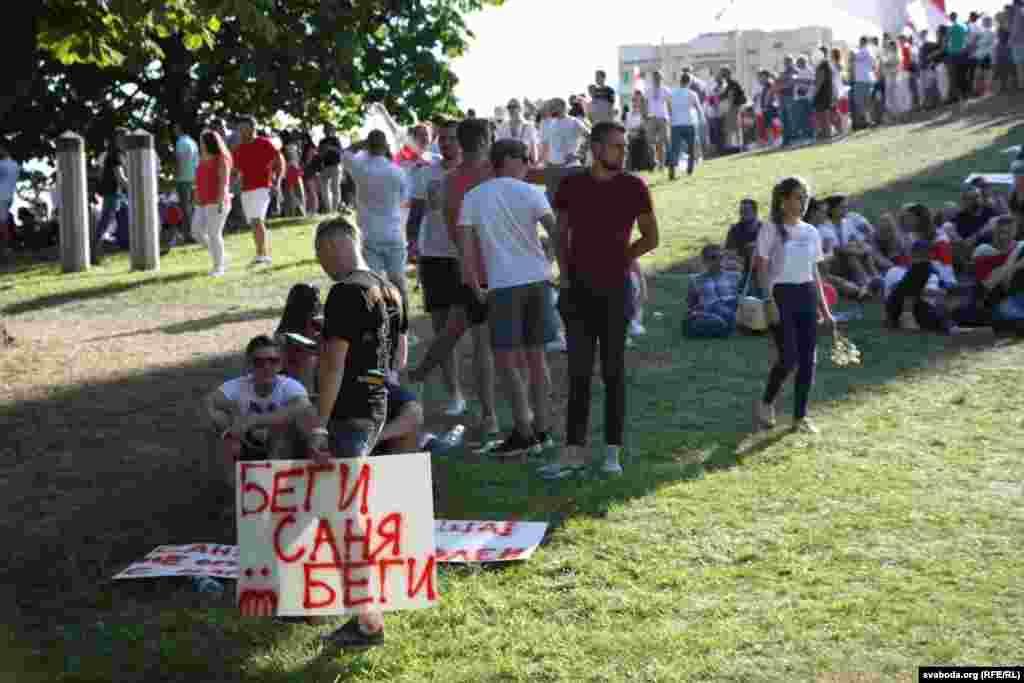 Демонстранти у Мінську, 17 серпня. Вони зупинилися на перепочинок. Чоловік тримає у руках плакат«Тікай, Саня, тікай»