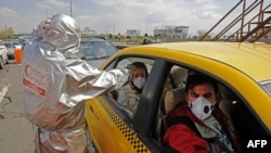 Members of Iranian Red Crescent test people with possible coronavirus Covid-19 symptoms, as police blocked Tehran to Alborz highway to check every car following ordered by the Iranian government, outside Tehran, March 26, 2020