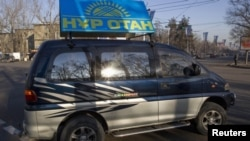 """Автомобиль с рекламным баннером партии """"Нур Отан"""" курсирует по улицам города Алматы. 11 января 2012 года."""