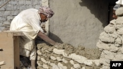 A quake survivor rebuilds a wall of his damaged mud-brick house in Awaran district. Many such houses are reported to be uninhabitable, if they didn't already collapse.