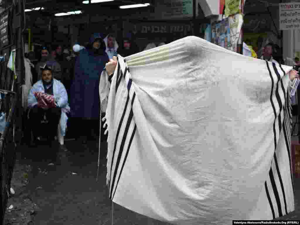 Під час шабату хасидам не можна фотографуватися і відволікатися на будь-що крім молитви та трапези. Цей прочанин закриває собою вхід до могили Цадика Нахмана, де моляться сотні прочан.