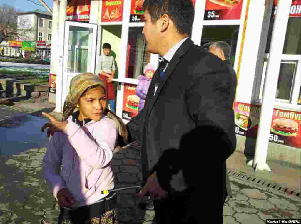 A security guard escorts a girl away from a restaurant.