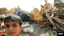 Iraq -- An Iraqi child stands next to discarded tank tracks as Iraqi employees from the Ministry of the Environment (unseen) visit a dump to measure the level of contamination on the outskirts of the southern city of Basra, 07Jul2009