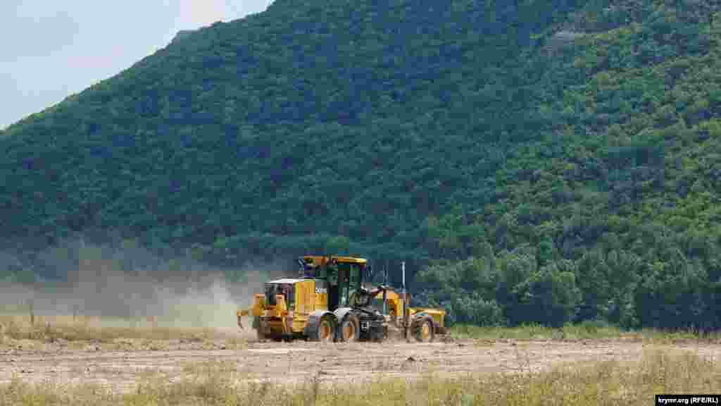 Грейдер расчищает новую площадку над рекой Альма
