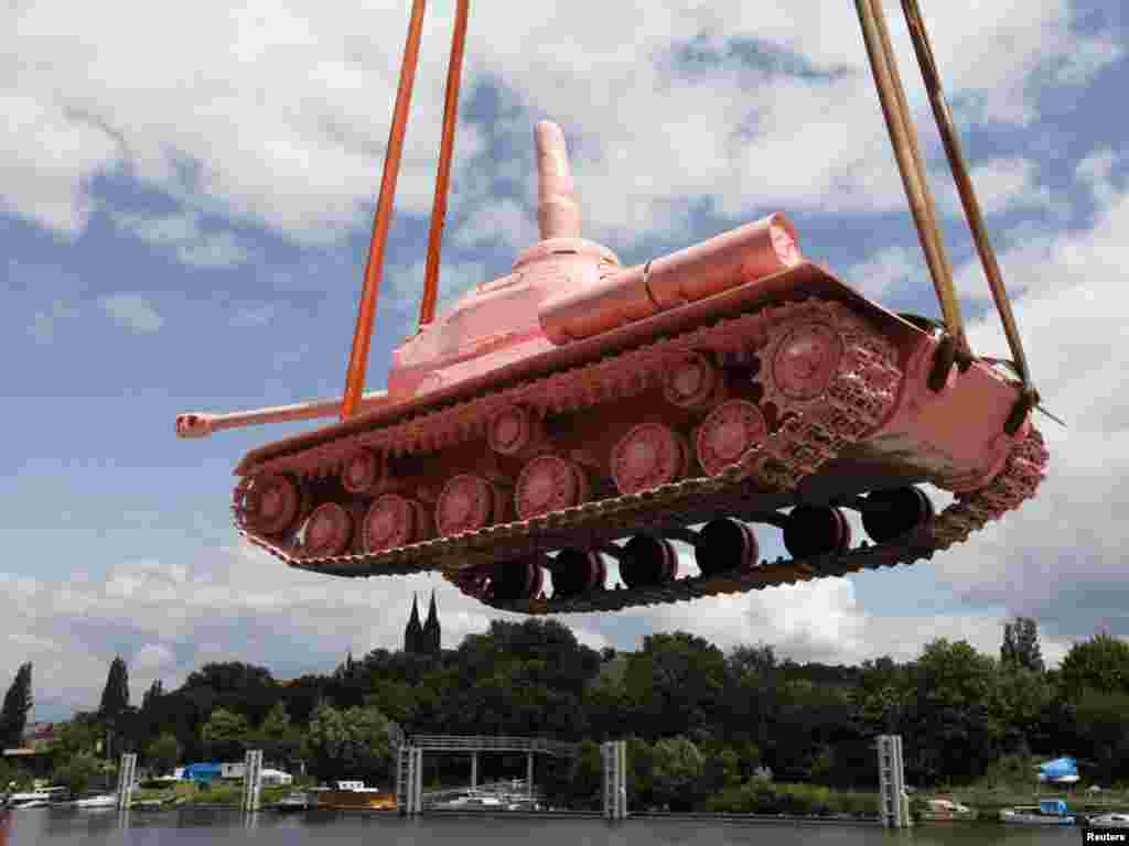 A Soviet WW II tank painted pink is loaded on a boat to be transported to Prague's city center on June 20. The tank had stood in Prague for more than 40 years as a monument to the Red Army's liberation of the city in 1945. Visual artist David Cerny controversially painted it pink in April 1991. The tank was brought back to Prague from a military museum as part of commemorations to mark the 20th anniversary of the departure of Soviet troops .Photo by Petr Josek for Reuters