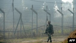 An Indian Border Security Force soldier patrols along the border fence at an outpost along the India-Pakistan border in Suchit-Garh on January 10.