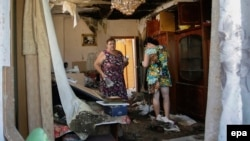 Local residents in Donetsk return to homes damaged by shelling in August.