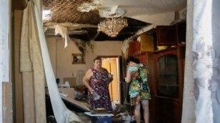 Жінки, які щойно повернулися з бомбосховища, оглядають пошкоджену внаслідок обстрілу квартиру. Донецьк, 2 серпня 2015 року