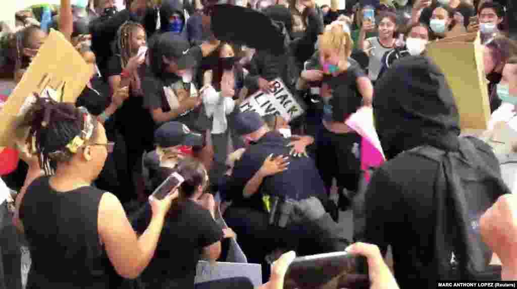 Шеф поліції міста Оклі Ерік Крістенсен обіймає протестуючого, стоячи на колінах перед протестувальниками. Оклі, штат Каліфорнія.(Фото з відео зі соцмереж. MARC ANTHONY LOPEZ /via REUTERS)