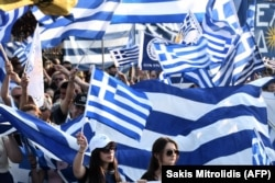 Protesters wave Greek flags as they take part in a demonstration to protest against the use of the name Macedonia in Pella on June 6.