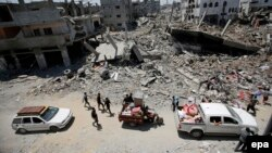 Palestinians carry their belongings next to the rubble of destroyed houses in Gaza City on August 1.