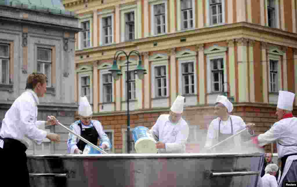 Bosnian chefs cook in a central square of the capital, Sarajevo, in an effort to set a record for the largest chicken broth for Guinness Book of World Records. (Reuters/Dado Ruvic)