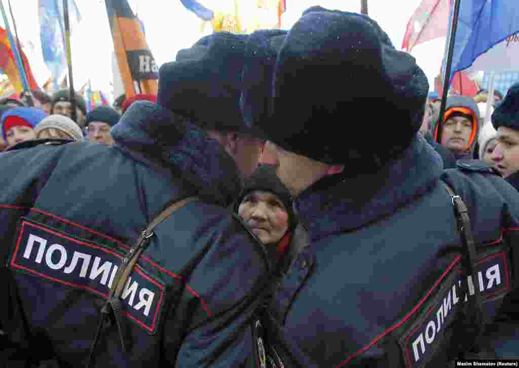 A woman watches Russian police officers during a March 18 concert in Moscow's Red Square marking the second anniversary of Russia's annexation of the Crimean peninsula. (Reuters/Maxim Shemetov)