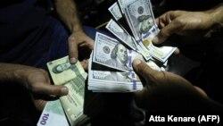 Банкноты номиналом 100 долларов США и 100 иранских риалов.