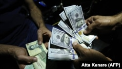 IRAN -- A man exchanges Iranian Rials against US Dollars at an exchange shop in the capital Tehran, August 8, 2018