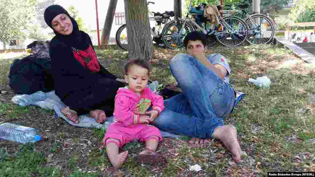 Syrian migrants take a break in a park.