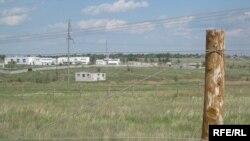 Протяженность казахстанско-российской сухопутной границы — более семи с половиной тысяч километров. На фото сквозь колючую проволоку виднеется окраина российского города Троицка.