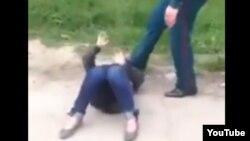 Скриншот видеозаписи, на которой инспектор Иззатилла Хашимов пинает лежащую на земле больную женщину.