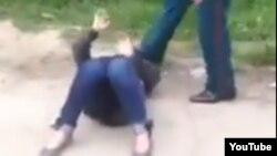 Узбекский милиционер пинает в лицо и голову лежащей на земле женщины.