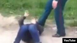 Сотрудник узбекской милиции пинает лежащую на земле пожилую женщину, архивное фото.
