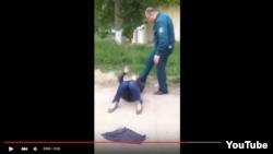 Иззатилла Хашимов пинает лежащую на земле русскую женщину.