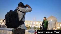 دو گردشگر جوان خارجی در میدان نقش جهان اصفهان، عکس یادگاری میگیرند.