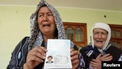 Босқын өзбек әйелі этникааралық қақтығыста қаза болған ұлының төлқұжатын көрсетіп тұр. Жалалабад, 21 маусым 2010 жыл.