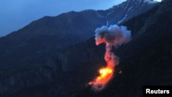 Two bombs explode at dusk on a Taliban fighting position above Kamdesh in Nuristan Province on June 11.