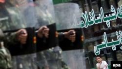 Мальчик-уйгур сидит возле магазина, наблюдая, как китайские солдаты идут по улице Урумчи, 12 июля 2009 года.