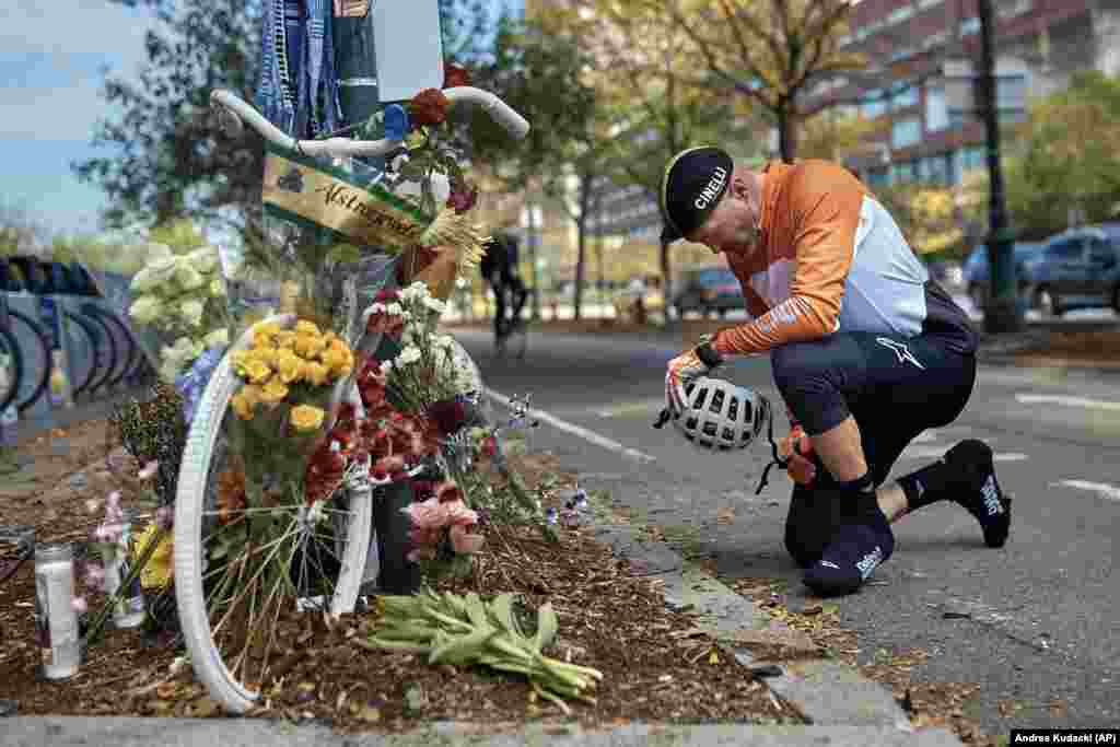 "A man prays after laying flowers at a ""ghost bike"" memorial that is now used to remember the victims of the deadly October 31 terrorist attack along a bike path in New York City. (AP/Andres Kudacki)"