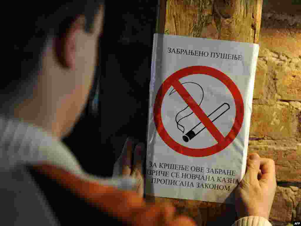 A barkeeper places an nonsmoking poster inside a Belgrade cafe on November 11. Serbia introduced on tough antitobacco measures, the strictest ever in the Balkans country, where some 33.6 percent of adults smoke. Photo by Andrej Isakovic for AFP