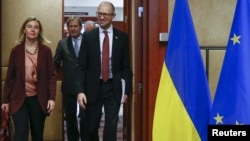 Прем'єр України Арсеній Яценюк (праворуч), єврокомісар із питань сусідства й переговорів щодо розширення Йоганнес Ган (посередині) і верховний представник ЄС із закордонних справ і політики безпеки Федеріка Могеріні. Брюссель, 7 грудня 2015 року