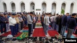 Мужчины во время молитвы на территории мечети