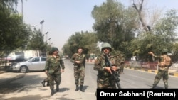 Security forces are seen near the site where a suicide bomber blew himself up in the center of Kabul on September 5.