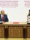 U.S. peace envoy Zalmay Khalilzad (left) and Mullah Abdul Ghani Baradar, the Taliban's top political leader, sign the peace agreement between Taliban and U.S. officials in Doha on February 29, 2020.