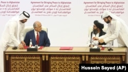 U.S. peace envoy Zalmay Khalilzad (left) and Mullah Abdul Ghani Baradar, the Taliban group's top political leader, sign a peace agreement between Taliban and U.S. officials in Doha on February 29, 2020.