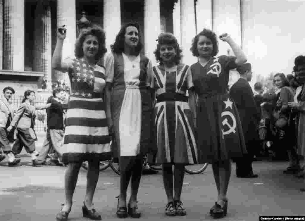 Women dressed in the flags of the United States, France, Great Britain, and the Soviet Union during celebrations in central Paris.