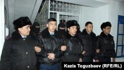 Полицейские и бойцы специального отряда полиции не пропускают наблюдателей и журналистов в зал судебного заседания, где ожидается оглашение приговора в отношении фигурантов дела «джихадистов». Алматы, 21 декабря 2018 года.