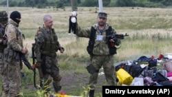 Боевик российских гибридных сил держит игрушку, обнаруженную на месте падения обломков «Боинга». Донецкая область, близ села Грабово, 19 июля 2014 года