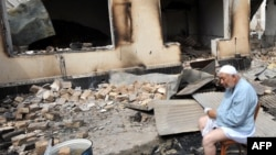 An elderly ethnic Uzbek man sits in front of his burned-out house in Osh.