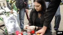 Students light candles near a portait of fellow student Ihor Indyl in Lviv in June.