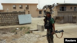 A member of an Afghan commando unit stands guard in a Kunduz district. (file photo)