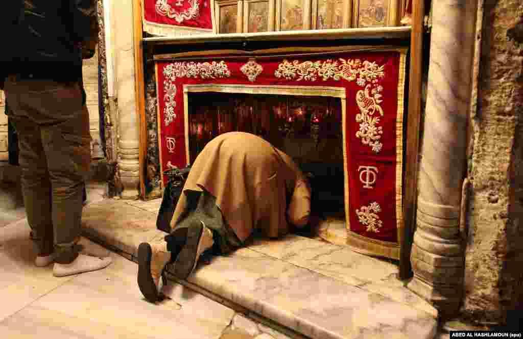 Женщина молится в церкви Рождества Христова в городе Вифлеем на Западном берегу Иордана. Грот в церкви христиане считают местом рождения Иисуса Христа