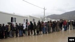 Гуманитарлық көмек кезегінде тұрған ирактықтар.