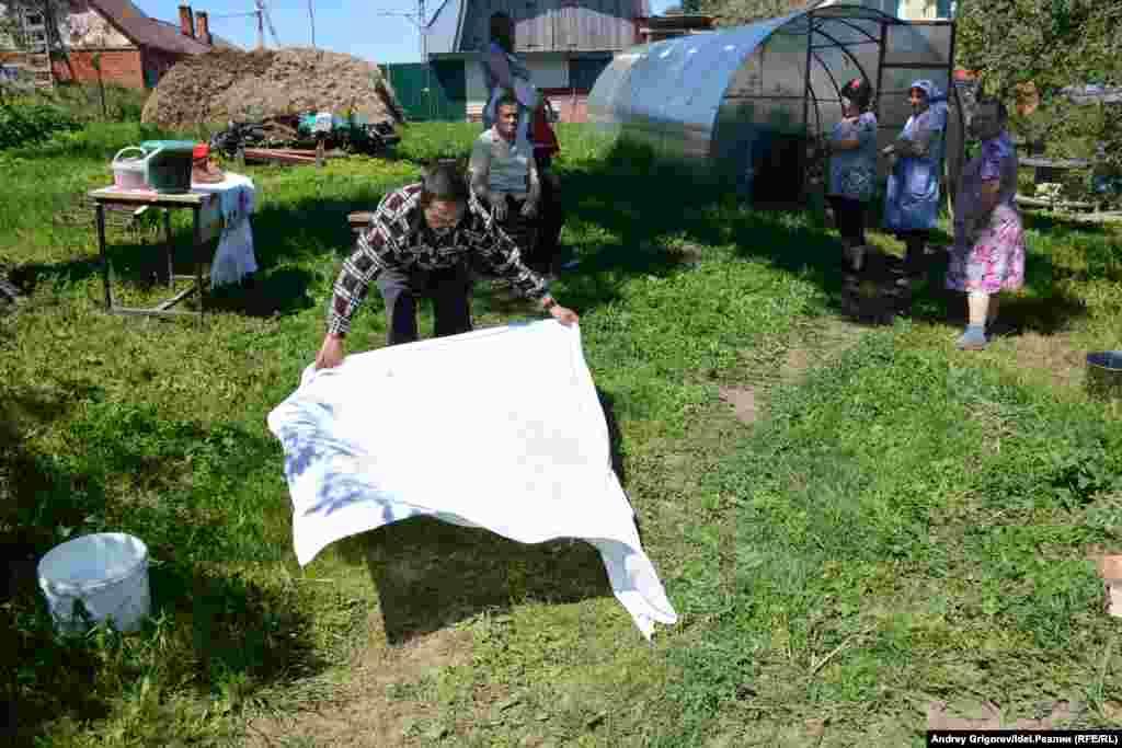 Эльмень расстилает покрывало, чтобы просеять зерно.