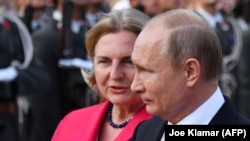 Russian President Vladimir Putin (right) and Austrian Foreign Minister Karin Kneissl take part in a wreath laying ceremony at the Soviet World War II memorial in Vienna on June 5.