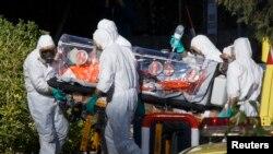 Испанские медработники переносят одного из двух миссионеров, заразившихся Эболой в Африке. Мадрид, август 2014 года.