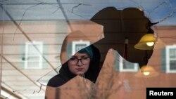 یکی از داوطبلان در فرگوسن در حال کمک به پاکسازی رستورانیست که هدف حمله معترضان قرار گرفت