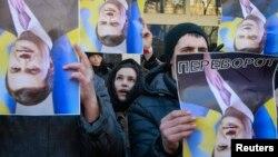 Сторонники евроинтеграции с перевернутыми портретами президента Виктора Януковича. Киев, 26 декабря 2013 года.