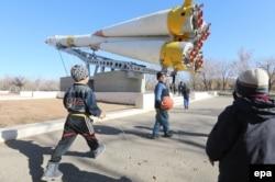"""Дети играют рядом с памятником ракете """"Союз"""". Город Байконур, 4 ноября 2013 года."""